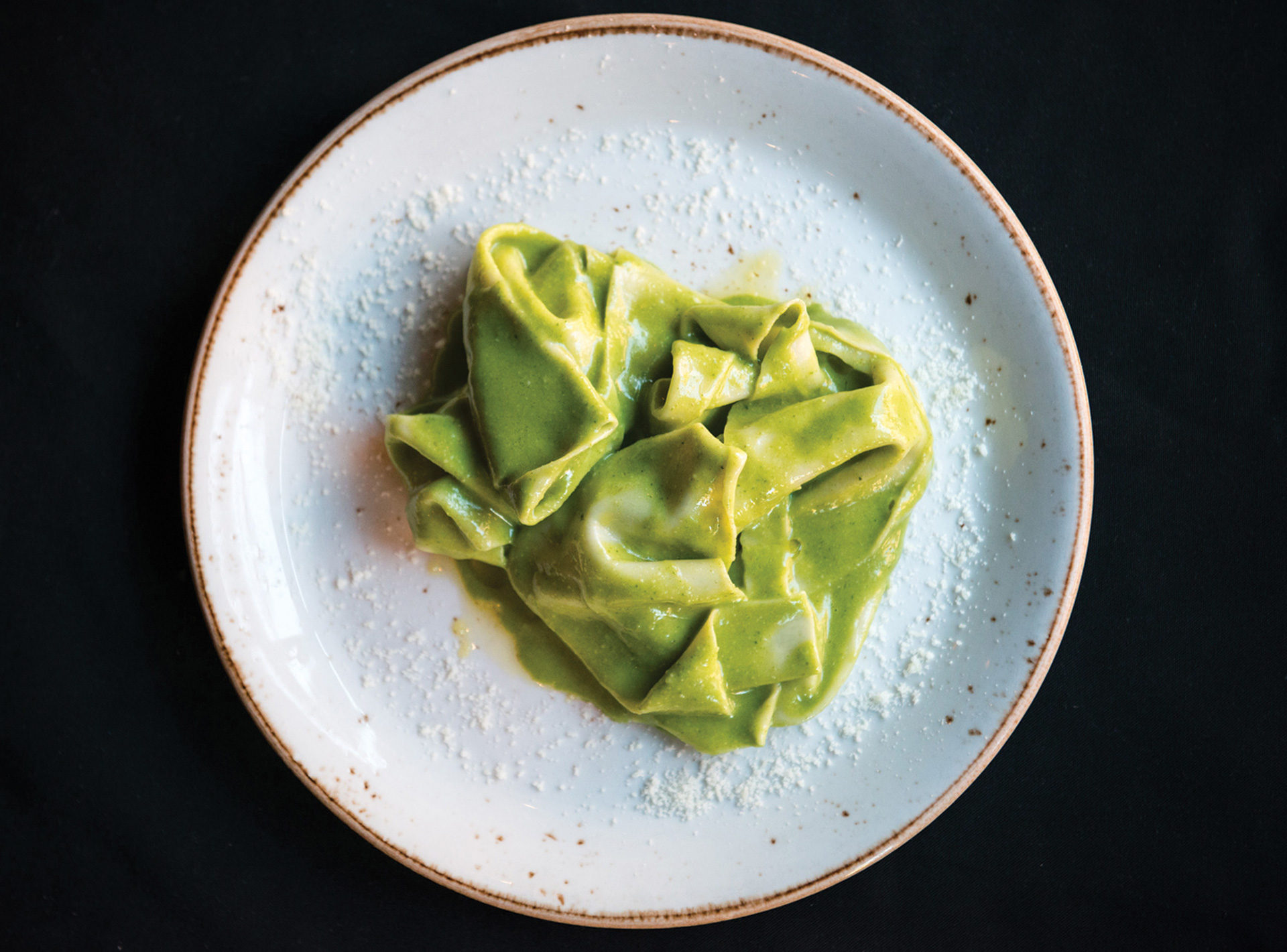 Top angle close up of our Mandilli di Seta, pillowy housemade hankerchief pasta, covered in delectable ligurian almond basil pesto
