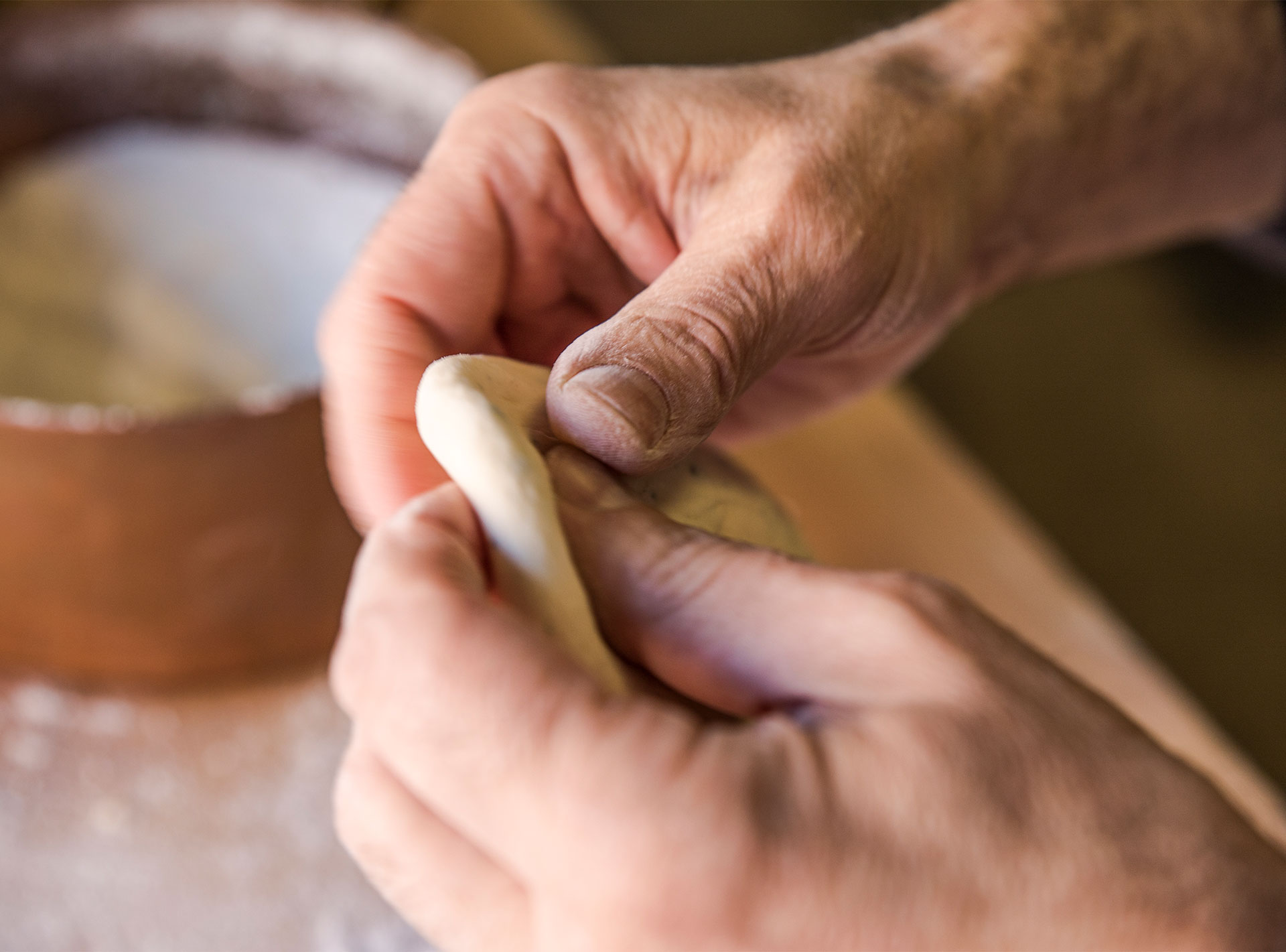 Closeup of hands preparing dough for an original Factory Kitchen pasta dish